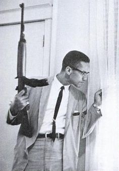 Malcom X holding a M1 Carbine and peering behind a curtain in response to death threats against him and his family.  1964