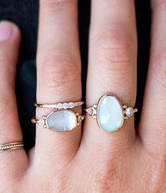 A beautifully elegant rosecut aquamarine stone is delicately accented with 2 side moonstones Set in a 14K Yellow Gold band Back bezel made of sterling silver to enhance the vibrancy of the stone Handm