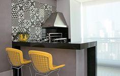 A arquiteta Ligia Resstom colocou estofado de couro sintético amarelo nos bancos altos Bertoia para contrastar com os acabamentos pesados da varanda. Como apoio para a churrasqueira, ela fez a bancada em L de granito preto e base cinza. Na parede, ladrilhos hidráulicos