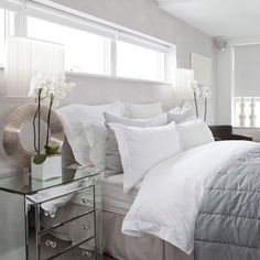 Stylish white bedroom Blending ice-white walls, bedlinen and roller blinds with cool dove grey accents gives a bedroom a chic, timeless appeal. Mirrored furniture, such as a chest of drawers, reflects light to add depth to the scheme. - Home Decor Like Mirrored Furniture, Bedroom Furniture, Bedroom Decor, Bedroom Ideas, Bedroom Designs, Mirrored Nightstand, Mirrored Bedroom, Bedside Lamp, Bedside Tables