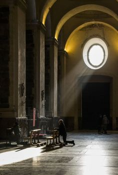 Worshippers praying at a side alter in the Duomo di Siracusa (Cathedral of Syracuse) in Ortygia, Sicily