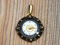 Small clock face pendant on a brace base.   Kleiner Ziffernblattanhänger auf einem Messinguntergund.