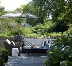 Outdoor living room.  Bluestone patio, cabana striped umbrellas, Moroccan lanterns.