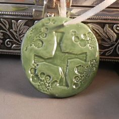 SALE!!! PRICE REDUCED FROM $8.00 DOWN TO $6.00    Round ornament featuring Brigids cross with small flowers around. All in a deep green color..