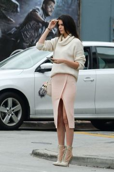In a creme oversized turtle neck paired with a fitted mid-length skirt.