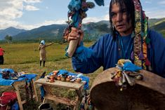 Photograph by Carolyn Drake  Oleg Dorzhiyev concludes the Bukha-Noyon ceremony with some two dozen other shamans in Siberia's Republic of Buryatiya as a woman flings a gift of milk toward the sacred rock on the hillside.