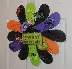 "Colors include orange,purple and black. Wreath is decorated with a green and purple daisy,spiders, a witch, and a sign that says ""If you're Trickin then I'm Treatin"" and it includes your witches shoes!. This wreath has 12 flip flops and measures approx. 22'-24"" in diameter. I hang my wreath on a regular sized door hanger, I can add a wire loop on the back for you to hang on the door hanger, I will at no charge-just message me in seller notes that you would like a wire loop on the back."