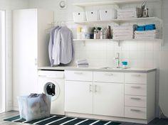 Tvättstuga med vita vägghyllor, bänkskåp med luckor eller lådor och ett högskåp med hyllplan på insidan