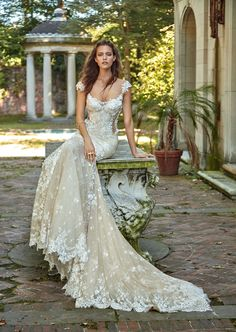 Galia Lahav: Vintage voluminous trumpet silhouette dress, made of novelty two toned lace, with antique crochet and 3D flowers adornments throughout the entire gown. It has a low open back and a triangular train.