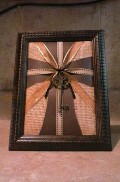 Framed ribbon cross on burlap with a key tied in the middle. (: This is a picture of the one I just made...