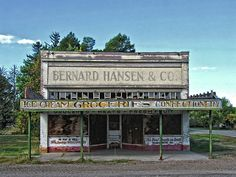 """""""General Store No More"""" Fine art photograph by Dilectus Rex. The old Bernard Hansen & Co general store sits abandoned and decaying on main street in the rural agricultural town of Bear River, Utah. The fading and deteriorating signs indicate ice cream, confections and other groceries are available but obviously the only thing you are likely to get out of this place is dust and dirt. #dilectusrex"""