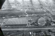 1970 - Parque Anhembi. Fotografia oblíqua do parque com destaque para o pavilhão de exposições, tomada nas proximidades do Rio Tietê (à frente) em direção ao Campo de Marte (ao fundo).