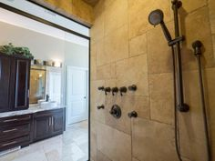 A spacious ensuite with a Travertine stone shower with body sprayers. Photo by Digital Video Listings.