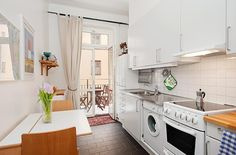 Swedish apartment with narrow kitchen.  Sink, washing machine, stove, counters on one wall.  Drop-leaf table on the other wall.