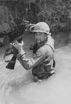 A combat photographer of the Americal Division (23rd Infantry Division) lifts his M16 above the water of a stream as he crosses.