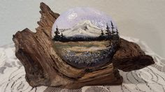 Mountain and Meadow Scene Painting on Rock displayed on log