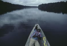 GABON. 1984. A young man rests on a boat cruising up the Ogooue River.