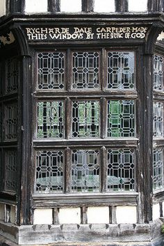 Section of the Withdrawing Room's bay window at Little Moreton Hall in Cheshire, England, showing an inscription identifying the carpenter.