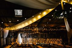 Rustic barn wedding in Devon. A bride's beautiful dress hung in the wedding breakfast room complete with twinkly fairy lights and bunting © Fairclough Photography