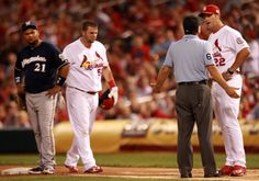 manager Mike Matheny talks with first base umpire Chris Guccione after a hit by Matt Adams was ruled a foul ball.   Cards won the game 5-1.  9-11-13