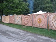 An encampment wall made of colourful tapestries or painted tarpaulins or sheets or summink.
