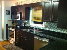 Dark brown cabinets with Black countertops....Love!
