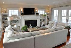 Un amplio salón donde un sofa-chaiselongue y unas butacas crean una zona en forma de U en torno a la televisión y chimenea.