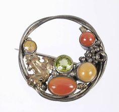 Dorrie Nossiter. An Arts and Crafts brooch with peridot, citrine and agate, with tendrils, beads and vine leaves. Sold by Dreweatt Neate.