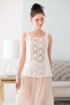 Worked with drop-stitch columns for an offbeat modern look, leaf-lace panels decorate the front and back of this sleeveless tank. The scoop neckline keeps it summery, while the A-Line silhouette and extended length make it a versatile layering piece that complements flowing skirts, slim capris and casual cut-offs. Sleek in mercerized cotton Vipe from Dale Garn/ Mango Moon, it's neatly trimmed with narrow garter-stitch borders.