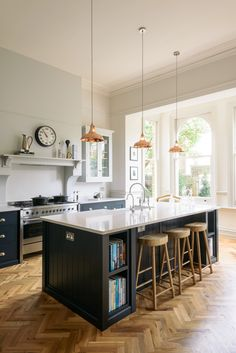 copper pendant lights hang above a beautiful big island in the Crystal Palace Kitchen by deVOL