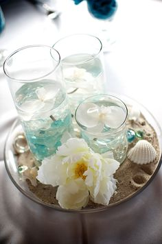 Beach centerpiece made with cylinder vases in sand and decorated with flowers, shells and aqua glass.