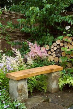 Stone bench on patio in backyard garden with flowers ferns privacy