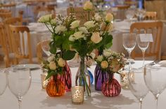 Tables at Upwaltham Barn decorated coloured bottles and stem vases filled with roses and scented geranium leaves.