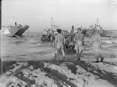 The Sicily Landings 9-10 July 1943: A tractor comes to the rescue of an armoured vehicle which had stuck in the mud temporarily during the invasion of Sicily, several landing craft can be seen in the background at dawn of the opening day of the invasion.