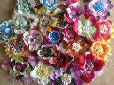 SpullieS bloemen broches. Recycling van: oude kunstbloemen (bloemblaadjes) restjes stof (yoyo's, enz.), vitragegordijn (witte romantische look tussenopvulling), knopen (hart van de bloem).