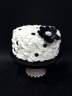 Black & White Wedding Cutting Cake - All chocolate cake with buttercream filling and frosting. Buttercream rosettes dotted with molded fondant roses. Black fantasy flower on top.