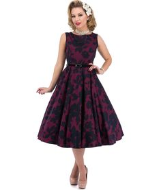 Beautiful 50's style Hepburn dress made from stretch Cotton Sateen fabric with a pretty navy blue floral design on a magenta / plum coloured background.  Fitted bodice with round neckline to front and back.  Full lower skirt.  Thin black suede effect belt to clench in waist.  Concealed zip to centre back.  Unlined.  The bodice and skirt are panelled and therefore the pattern won't match up at the seams.  Made in England   To make the dress fuller (as in the main image) wear with a Hell...