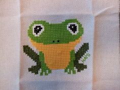 Cross stitching frog for a little baby