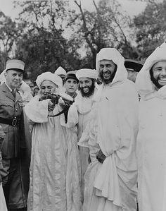 1943, Algérie française, Ali Pacha, chef berbère tire avec une mitraillette Thomson entouré d'autres Berbères et d'officiers de l'armée française