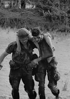 Dong Tam, South Vietnam 1967: A wounded 9th  division soldier, whose body was booby trapped by the Communists is  helped to safety after the traps were removed. He was injured during  fighting in the Mekong Delta area.