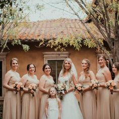 Bridesmaids wearing floor length strapless David's Bridal champagne dresses holding bouquets of peach roses   Ethan Beazley   villasiena.cc