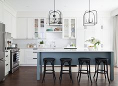 Hid the bulkhead (soffit) with a riser and crown molding that match cabinets, color scheme, cabinet style and hardware, simple range hood blends with cabinets, lights above island | Vanessa Francis Design