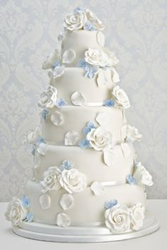 "White Rose' wedding cake    : Madagascar vanilla bean cake,  vanilla bean buttercream, raspberry preserve, Satab ribbon,  handmade sugar roses and hydrangea flowers.    (for alternatives please see 'Fillings & flavours')    Price as shown:  5 tiers (4"", 6"", 8"", 10"", & 12"")  £1225"