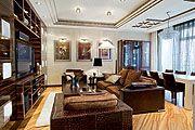 Общий вид гостиной. Теплые шоколадно-коньячные оттенки  в сочетании с праздничным белым, разнообразные подсветки  и дорогие фактуры создают ...