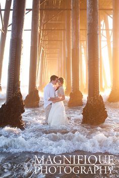 www.magnifiquephotography.com  Bride and Groom in the water under pier
