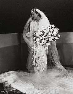 Joan Crawford wedding gown from the 30s.  Bias cut, flowing gown with train.  Long, flowing veil and an enormous cascading floral bouquet
