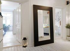 biały korytarz,duże czarne lustro,lampion,wąski przedpokój,biały przedpokój,korytarz,jak urzadzić wąski korytarz,biale ściany,skandynawski styl,nowoczesne mieszkanie,dekoracja holu,dekoracje do przedpokoju,typografie,czarny chodnik,dywan w przedpokoju,biała podłoga
