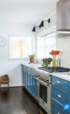 Liven up your kitchen with brightly painted cabinets like the blue ones in this space.