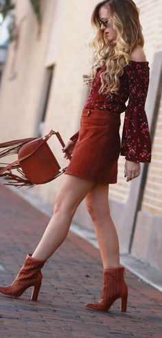 Casual 70's inspired outfit styled with suede mini skirt, floral bell sleeve top, cognac booties, and fringe bag