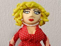 Linda boneca Marilyn Monroe, feita em garrafa Pet de 600 ml, tecnica de papietagem moldando o corpo e braços. Colo, busto, cabeça e cabelos em biscuit. Aplicação de vestido, de tecido de algodão, chale de fita ,brincos e colar imitando pérolas. Pintura decorativa. Braços articulados. Base em MDF. Altura: 27 cm largura frente: 8cm largura lado: 10 cm Aproximadamente 250 gramas R$40,00